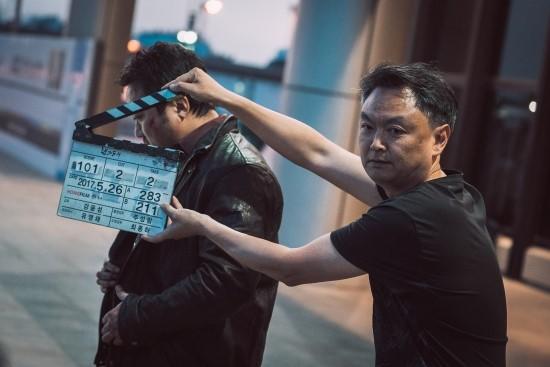 촬영 현장에서 슬라이드를 들고 있는 강윤성 감독 모습